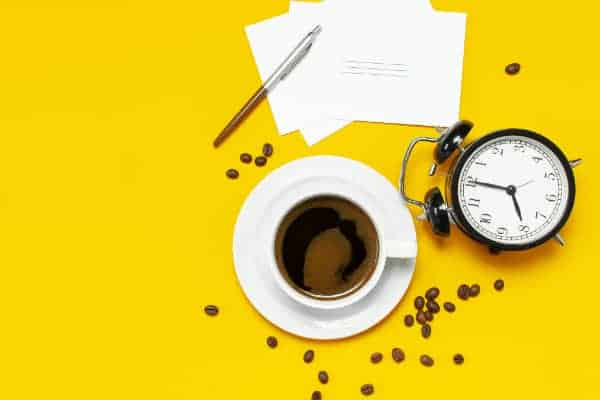Flat lay cup black coffee, coffee beans, black alarm clock, pens, white cards on yellow background top view copy space. Creative Concept time to work, female desktop, coffee background.